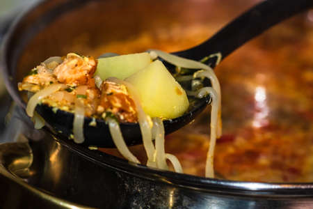 Preparation of soup with chicken and vegetables. Close up of boiling soup, focus on spoon with noodles and vegetables. Stock fotó