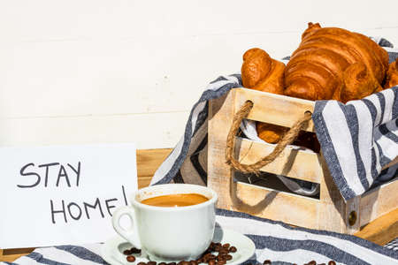 """Coffee cup and buttered fresh French croissant on wooden crate. Food and breakfast concept. Morning message """"stay home"""" on white board"""