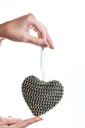 Hand holding heart shaped decoration isolated on white. Imagens
