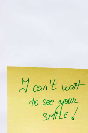I can not wait to see your smile handwriting text close up isolated on yellow paper with copy space.