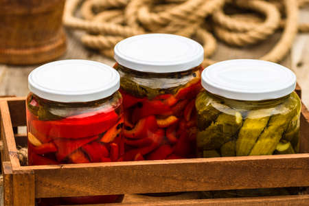 Wooden crate with glass jars with pickled red bell peppers and pickled cucumbers (pickles) isolated. Jars with variety of pickled vegetables. Preserved food concept in a rustic composition. Standard-Bild