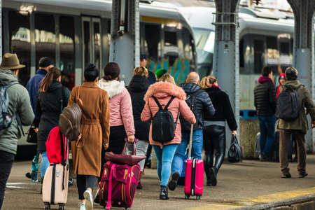 Travelers and commuters carry luggage and backpacks on the train platform of Bucharest North Railway Station (Gara de Nord Bucharest) in Bucharest, Romania, 2020