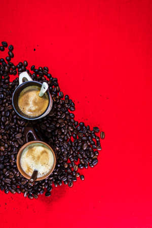Cup of coffee, roasted coffee beans on red background, top view, copy space for text, coffee concept, close up coffee photo