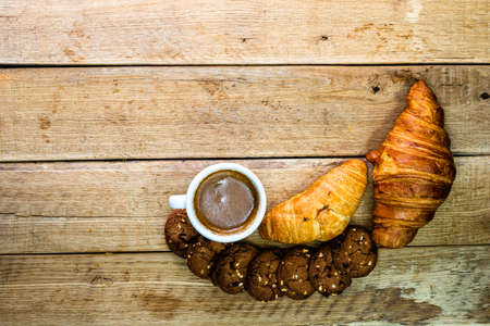 Fresh croissant, puff pastry and biscuits on wooden table. Coffee, food and breakfast concept. Desserts, fresh pastries and coffee. Top view and copy space