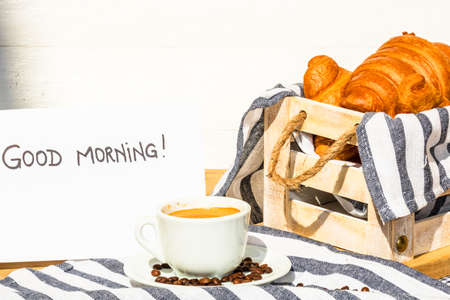 """Coffee cup and buttered fresh French croissant on wooden crate. Food and breakfast concept. Morning message """"good morning"""" on white board Zdjęcie Seryjne"""