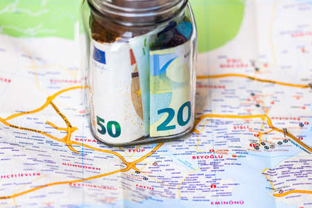 Composition with saving money banknotes in a glass jar. Concept of investing and keeping money for dreams and travel, close up isolated. Standard-Bild