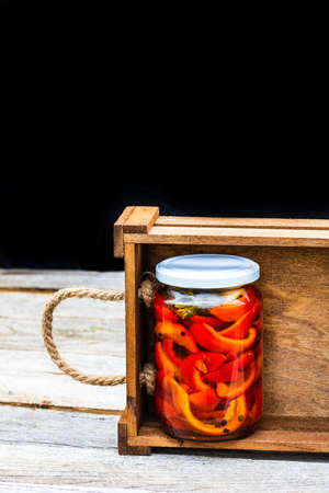 Wooden crate with glass jars with pickled red bell peppers.Preserved food concept, canned vegetables isolated in a rustic composition. Standard-Bild