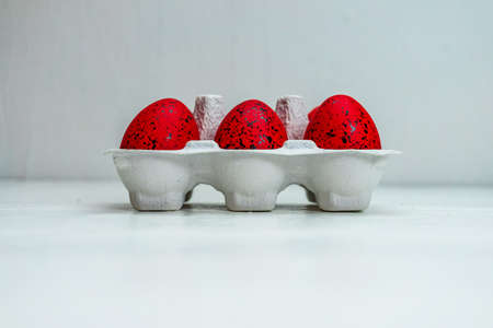 Easter set with red and  black ornated eggs in carton isolated on white background with copy space.