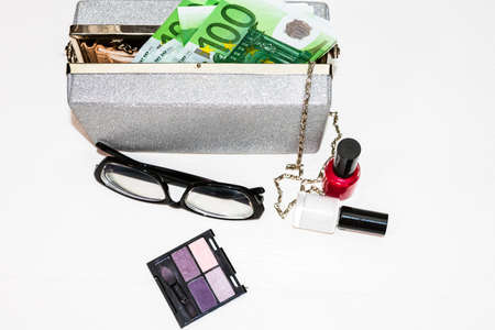 Glittery silver clutch bag with money and beauty products isolated on white background with copy space.