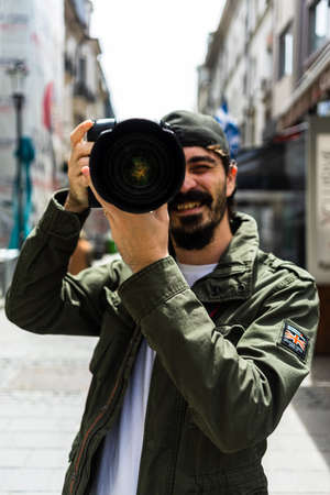 Street photographer taking photos with DSLR camera and telephoto lens in Old Town of Bucharest, Romania, 2020 Editöryel