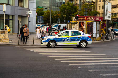Romanian police (Politia Rutiera) car patrolling streets to avoid curfew breaches amid the spread of the COVID-19 in downtown Bucharest, Romania, 2021 Editöryel