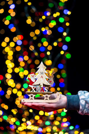 Woman's hands hold christmas decoration. Christmas and New Year holidays background, winter season with Christmas ornaments and blurred lights Imagens
