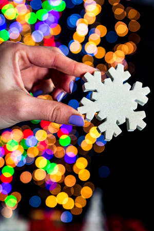 Holding Christmas snowflake decoration isolated on background with blurred lights. December season, Christmas composition. Imagens