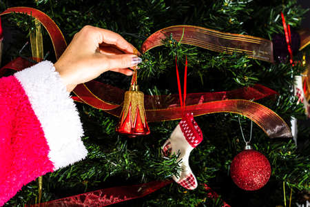 Decorating Christmas tree, hand putting Christmas decorations on fir branches. Christmas hanging decorations.