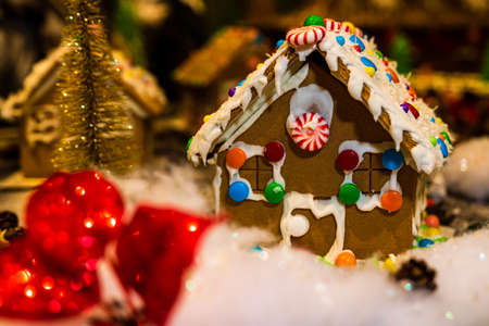 Colorful gingerbread house isolated on blurred background with Christmas decoration. Imagens
