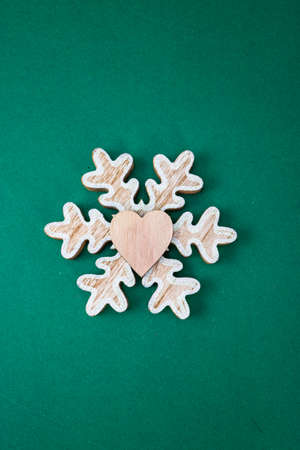 Snowflake Christmas decoration on green background. Top view with copy space for december season. Imagens
