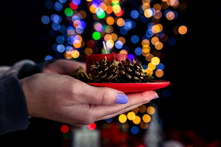 Holding Christmas decorated candle isolated on background with blurred lights. December season, Christmas composition.