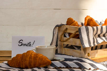 """Coffee cup and buttered fresh French croissant on wooden crate. Food and breakfast concept. Morning message """"smile"""" on white board"""