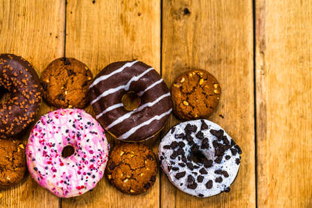 Colorful donuts on wooden table. Sweet icing sugar food with glazed sprinkles, doughnut with chocolate frosting. Top view with copy space