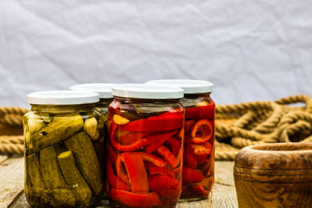 Glass jars with pickled red bell peppers and pickled cucumbers (pickles) isolated. Jars with variety of pickled vegetables. Preserved food concept in a rustic composition.