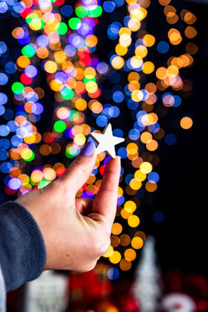 Holding Christmas glittery star decoration isolated on background with blurred lights. December season, Christmas composition.