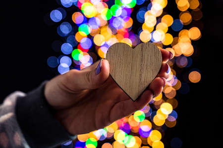 Holding Christmas heart shape decoration isolated on background with blurred lights. December season, Christmas composition.