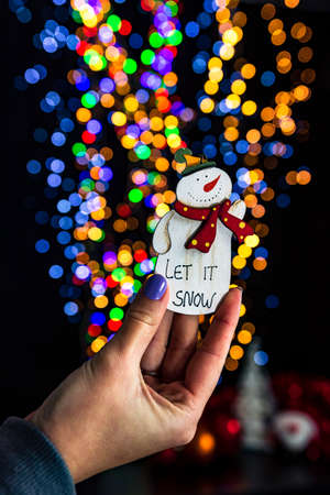 Holding Christmas snowman decoration isolated on background with blurred lights. December season, Christmas composition.