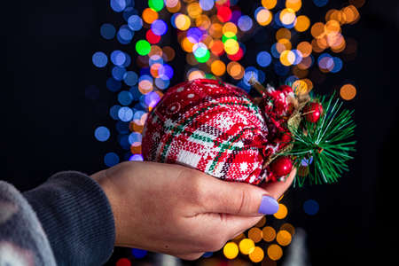 Holding Christmas bauble decoration isolated on background with blurred lights. December season, Christmas composition. Imagens