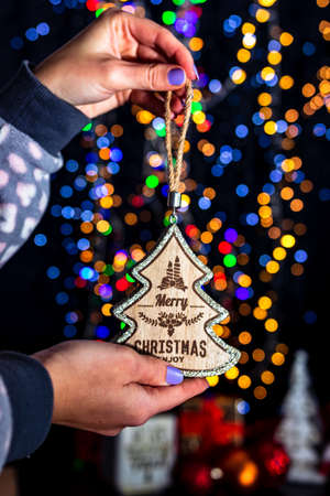 Holding Christmas decoration isolated on background with blurred lights. December season, Christmas composition. Imagens