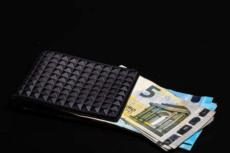 5 Euro money banknotes in black wallet isolated