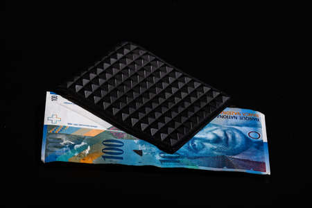 100 swiss franc banknote in a black wallet isolated.
