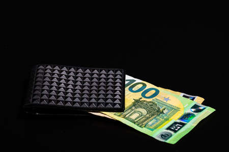 100 Euro money banknotes in black wallet isolated