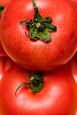 Close up of ripe red tomato, tomatoes background.