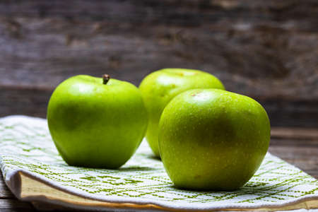 Detail on ripe green apples on wooden table.