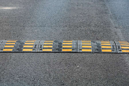 Traffic safety speed bump on an asphalt road in a parking area in Bucharest, Romania, 2020
