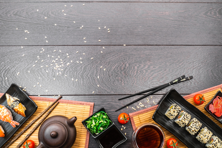 Sushi set sashimi, nigiri, maguro and sushi rolls served on plate with teapot and tomatoes on dark wooden background. Space for text. Stock Photo