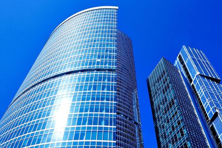 Modern skyscraper business center on blue sky background photo