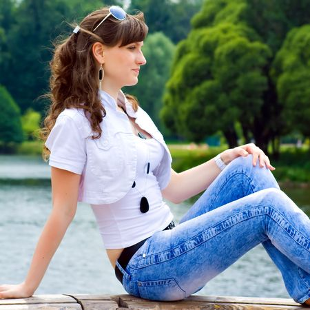 Pretty smiling girl sitting on bench photo