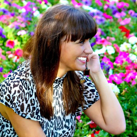 Pretty smiling girl talking with phone in flowers photo