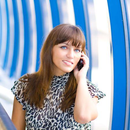 Beautiful confident businesswoman indoor glass corridor talking by phone photo