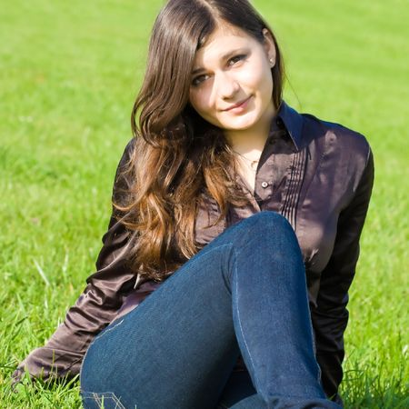 lay down: Pretty smiling girl sitting on the meadow