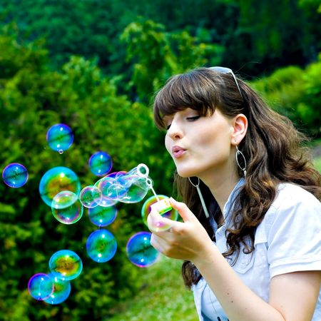 Young girl blowing soap bubbles in summer green park Stock Photo - 5676061