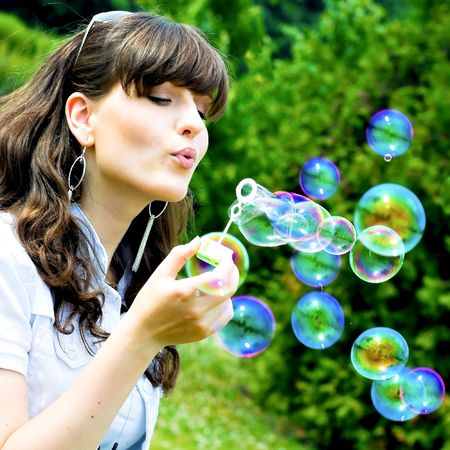 attractive girl blowing soap bubbles in summer green park photo