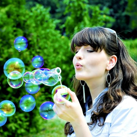 Young girl blowing soap bubbles in summer green park Stock Photo - 5751595