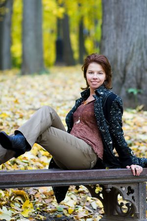 Beautiful young woman in autumnal park photo