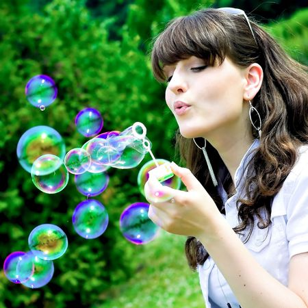 girl blowing: attractive girl blowing soap bubbles in summer green park