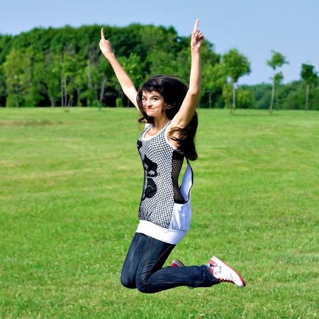 smile teen open hands jumping on the meadow photo