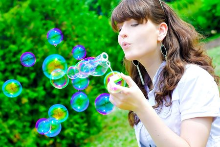 Young girl blowing soap bubbles in summer park photo