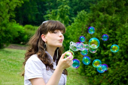 smile teen with soap bubbles in vivid green spring forest park photo