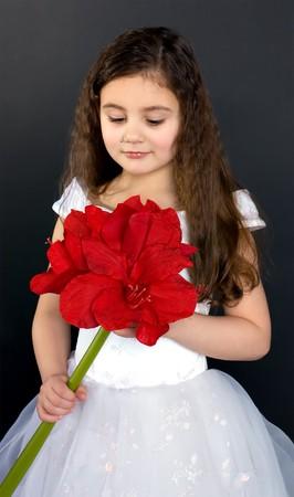belle fille rêve avec une fleur rouge vive
